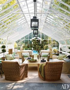 The greenhouse turned pool cabana in interior designer Timothy Corrigan's 1930s Lake Forest, Illinois, home features a seating area with wicker chairs gathered around a cocktail table of his design.
