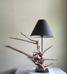 This beautiful driftwood table lamp, brings the beach inside with its unique but modern design. The lamp itself features beautiful sun bleached driftwood root ball left with its natural patina. The lamp has a flat black metallic base with supportive balls to save your tables. The shade is not included with this listing as I want to give you the opportunity to match to your decor scheme. The lamp is turned on with a flick switch located on the lamp cord which is black in color. A beautiful…