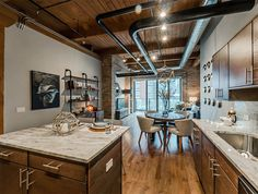 Timber beams, 12-foot ceilings, and exposed brick preserved this Streeterville loft's industrial character, while a high-end kitchen makes for comfortable and convenient living. #streeterville #loft