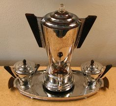 Manning-Bowman coffee service made of chrome with catalin trim. Extreme styling that screams the power and optimism of the Machine Age Art Deco era in the United States. Chrome is tarnished in sections (can be seen in photo) but the rarity of this set and it's very desirable design make this a highly collectible coffee service. Includes coffee pot, electric cord, creamer, sugar, and matching tray.
