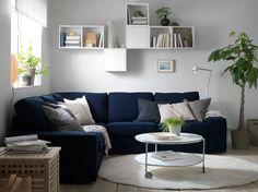 Uma sala com um sofá de canto azul com almofadas em bege, cinzento e preto. Também com uma mesa de vidro redonda com rodízios, sobre um tapete redondo com pelo comprido.