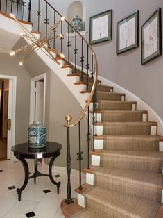 Designed by Matthew Moore, this winding staircase with a gold banister features floral sketches and pottery on the adjoining wall. The gold motif is echoed in the starlike modern chandelier hovering in the foyer.