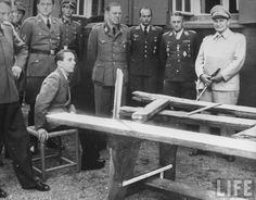 Joseph Goebbels sitting on a chair while Hermann Göring looks on. Both are looking at the destroyed conference table used when a bomb went off intending to kill Adolf Hitler on 20 July 1944