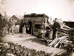 Camp of the 6th N.Y. Artillery at Brandy Station, Virginia, showing Union soldiers in front of log company kitchen.