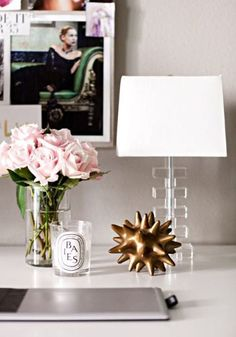 15 Things Every Single Fashion Blogger Has on Her Desk - Pink flowers, a Diptyque candle, lucite lamp + gold sea urchin paper weight