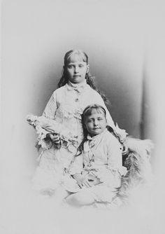 Princesa Marie (à direita) sentado, a perna esquerda dobrada sob sua direita; ela olha para frente. Princesa Alix está à direita de Marie, seu braço esquerdo em volta dos ombros de Marie, uma boneca em sua mão direita. Elas usam vestidos idênticos. Julho de 1878.
