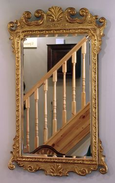 Wall Mirror - Nineteenth century gilt wood pier mirror, bevelled plate glass and carved scroll work frame surmounted with a shell.  circa. 1860