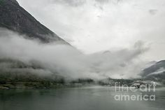 Cruise ship docked in Geiranger in a foggy and cloudy day, Norway