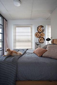 A cadela Amelie guarda a cama da dona. Atrás, na parede, a luminária escultórica da Prototype (Foto: Marco Antonio/ Editora Globo)
