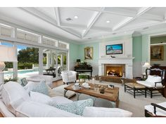 Beachy turquoise Family Room with white ceiling beams - Olde Naples