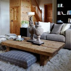 A cosy shaggy rug is perfect for this country-cottage style living room. A low coffee table and cushions are perfect for sitting around with friends and family. A grey sofa is updated with shimmering cushions, while a black bookcase is ideal for keeping books and accessories on display.
