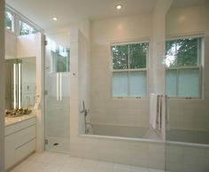 Contemporary white marble title master bathroom maximize stunning views of rugged Maine.