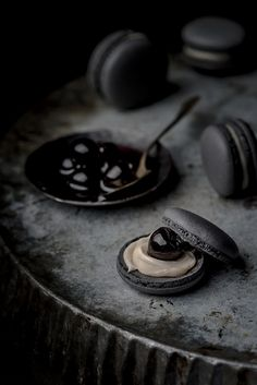 Black macarons filled with white chocolate ganache and black cherries in syrup.