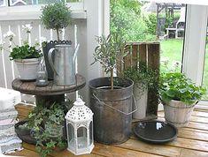Pequeno carretel de madeira usado como mesa de plantas na varanda