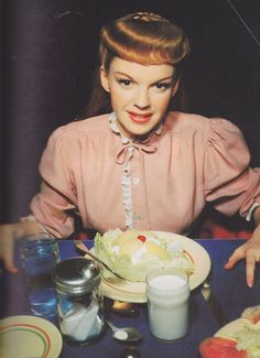 """Judy looks rather unhappy in this picture. Maybe it's because she's starving--this is probably her first real meal on the set of """"Meet Me in St. Louis."""" she had to get down to 98 pounds for the film!"""