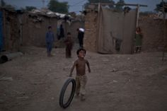 Afghan #refugee boy, Mohammed Farhan, 6, plays with a tire on the outskirts of #Islamabad, #Pakistan. (AP Photo/Muhammed Muheisen)