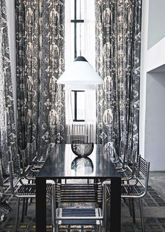 Sleek dining space with all black table and metal chairs, floor to ceiling black and white patterned drapes, and a white pendant light fixture.