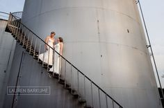 Two brides climb an industrial tower in their couple photo shoot at Rovos Rail Train Station. Pretoria, South Africa. LGBT Wedding photography by Lauren Barkume www.laurenbarkume.com