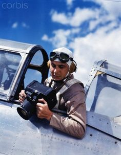 1940s army air corps crewman sitting in airplane cockpit wearing flying goggles helmet coveralls and parachute taking photographs with aerial camera - 42-32404302 - Rights Managed - Stock Photo - Corbis