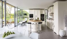 This indoor-outdoor kitchen with bi-fold doors is the perfect addition to any home, featuring a contemporary take on a traditional shaker kitchen design.
