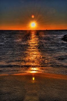SKY LIGHTS - The early morning sun rising over the ocean makes the grains of sand look like flecks of gold and reflects off the water on the beach earth- Enlarge to see! #DianaDee:) MOST #POPULAR RE-PINS  -  http://www.pinterest.com/DianaDeeOsborne/sky-lights/ - Orange Sunrise on the sea, with another odd orange light ball above the sun, reflected on the wet sand of the beach. Ocean waves gently slap the land. Unusually dark stormy like early morning photograph. CREDIT: Nickologist on…