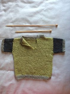 A short sleeved baby sweater,  hand knitted in 70% linen, 30% Pima Cotton.