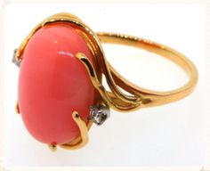 SOLD. Pink coral cabochon ring.  This is such a pretty ring! The 14K yellow gold mounting swirls around the oval pink cabochon and two small diamonds add a touch of whimsy. The coral measures 16 X 12mm. Finger size is 7.