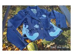 """#sweetolivecouture One of a kind, restyled, fitted denim jacket, size Medium. turquoise blue embroidered embellishments on front and back. Iridescent thread used to highlight the embroidered details. One of a kind, eco friendly. This piece is super cute with gathered pocket detail and elbow patches.   Shoulder 47"""" Chest 42"""" Front length 13.5"""" Arm Length 24.5""""  https://www.etsy.com/listing/211376821/turquoise-blue-embellished-denim-jacket?ref=shop_home_active_5"""