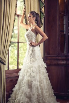Halter-style gown with organza ruffled skirt by Justin Alexander. #ruffle #wedding #dress