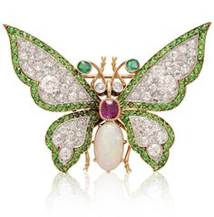 AN ANTIQUE GEM-SET BUTTERFLY BROOCH  Set with an oval cabochon opal and cushion-cut ruby body, extending old European-cut diamond and demantoid garnet wings, diamond collet eyes and emerald collet antennae, mounted in platinum and gold, circa 1890's