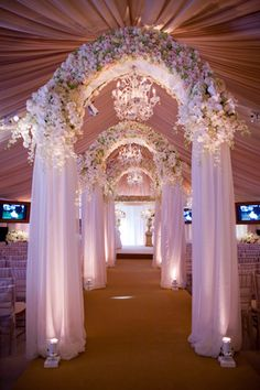 Gorgeous floral and curtain wedding arch inside of the large tent for the ceremony. The carpet is my least favorite, however the lights on each side of the arch as well as the ceiling gives the stunning arch an unbelievable glow.