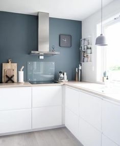 peinture bleu canard cuisine bleu canard meuble bleu canard, meubles en blanc, sans poignées, aspirateur en inox, horloge de cuisine au mur