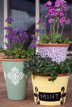 Transforming terracotta pots using outdoor paint, a smooth paint roller, foam stamp, and chalkboard paint. DIY. More info here.