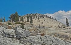Olmsted Point, located in Yosemite National Park, is a viewing area off of the Tioga Road which offers a view into Tenaya Canyon. This view looks southwest into the valley, giving, in particular, a view of the northern side of Half Dome and a view of Tenaya Lake to the east. Here, three visitors hike up the adjacent dome to the north