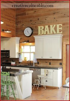 Love this cabin kitchen. White cabinets and I like the support for the island countertop which looks like concrete.