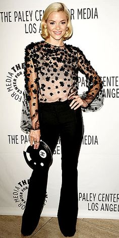 actress wears a rosette-adorned sheer blouse with wide-leg trousers, Jimmy Choo wedges and cocktail rings.