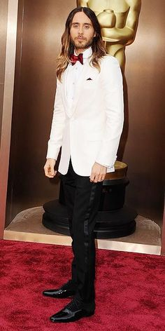 """Jared Leto wore a cream jacket, white shirt and black tuxedo pants with a burgundy bow tie by Saint Laurent by Hedi Slimane. """"I always love that old school vibe and I never wear suits. [This is] something classic,"""" the """"Dallas Buyers Club"""" actor told Ryan Seacrest. http://www.people.com/people/special/0,,20783495,00.html#54&id=1582668"""