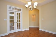 Doors lead to office; arched door to master bedroom.  Photographer is standing in the dining room.