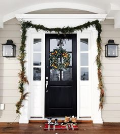 """Siding is Sherwin Williams """"Intellectual Gray"""" and the door is """"Tricorn Black."""" Trim is Ben Moore White Dove. Lights from Shades of Light."""