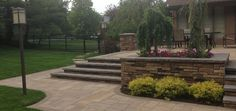 Elevated patio with integrated retaining wall. Built using @techobloc pavers.