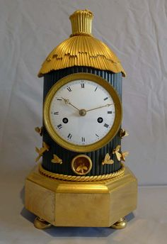 """Antique French Empire """"Genre"""" mantel clock """"La Ruche"""" in patinated bronze and ormolu. The clock stands upon four ormolu bun feet, the base is hexagonal in form. The main body of the hive is in patinated bronze and its cylindrical form is reeded, with the movement and dial inserted into the centre. The twist to the top of the thatched roof forms a little turret with a single ormolu bee at rest. Around the entrance are fixed several other ormolu bees. Circa 1805-10."""