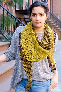 This two-color asymmetrical, curved triangle shawl begins at one narrow end and…