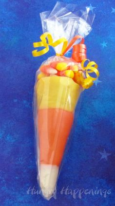 Candy Corn Cones - Dress up plain sugar ice cream cones dipped in candy melts this Halloween.