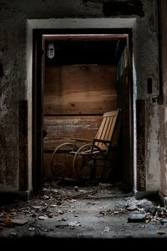 Antique wooden wheelchair in abandoned asylum elevator; Verden Psychiatric Hospital