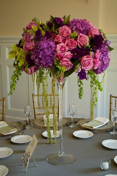 """A beautiful floral centerpiece. A glass vase like this will not block any views, but will still add a """"wow"""" factor to your reception."""