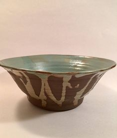A handmade pottery stoneware bowl. The bowl measures 4.25 inches tall by 10 inches wide at the top. The primary color of the food-safe glaze is turquoise blue/green. This bowl is wheel thrown with a chocolate-colored clay.