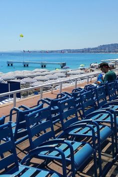"""These blue chairs line parts of the seafront boulevard, the Promenade des Anglais, in Nice, France.  They are a well known symbol of the city.  You can see why the coast is called the """"azure"""" coast, la côte d'azur, in this picture as it's always a beautiful vibrant blue."""
