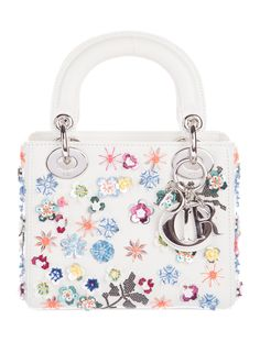 From the 2015 Collection. Ivory leather Christian Dior Mini Lady Dior bag with gunmetal hardware, detachable flat shoulder strap, dual flat top handles, multicolor floral-sequined embellishments throughout exterior, cobalt leather interior lining, single interior wall pocket with zip closure and interior flap closure at top. Includes dust bag. Shop Christian Dior designer bags online at The RealReal.