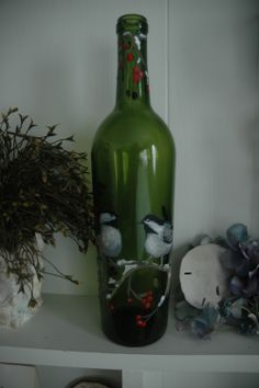 Here is a wine bottle that I painted two chicadees on.  Sitting on a branch with berries and snow.  There are tiny fairy lights inside the bottle, too.  SOLD