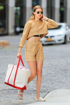 Gigi Hadid wearing a cropped camel sweatshirt and shorts and espadrilled while out in NYC.